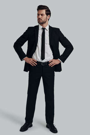 Ready to do business. Full length of handsome young man in full suit looking at camera and keeping hands on hips while standing against grey background