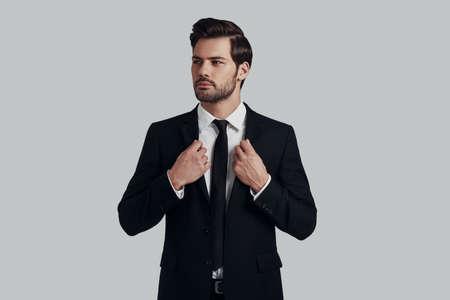 Confiado en su estilo. Apuesto joven en traje completo ajustando la chaqueta y mirando a otro lado mientras está de pie contra el fondo gris Foto de archivo