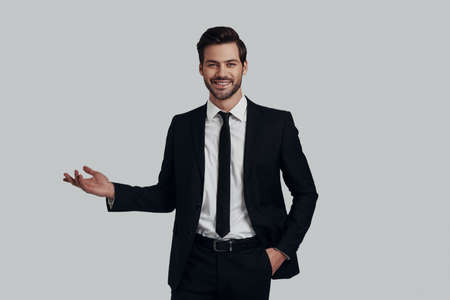 Just take a look! Handsome young man in full suit pointing copy space while standing against grey background