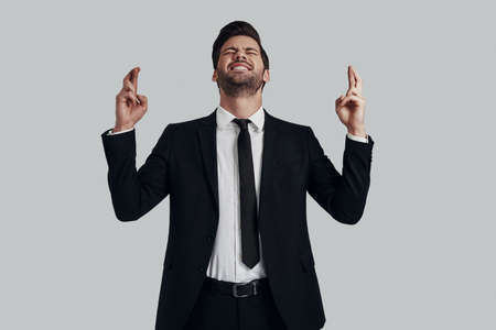 I wish? Handsome young man in full suit keeping fingers crossed and eyes closed while standing against grey background