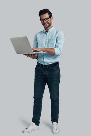 How may I help you? Full length of young man using laptop and looking at camera with smile while standing against grey background