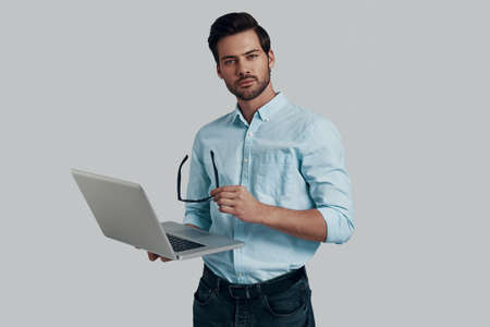 Can I help you? Handsome young man using laptop while standing against grey background