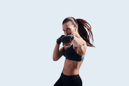 Boxing power. Attractive young woman looking at camera and boxing while standing against grey background Banco de Imagens