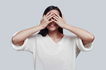 See nothing. Attractive young woman covering eyes with hands and smiling while standing against grey background