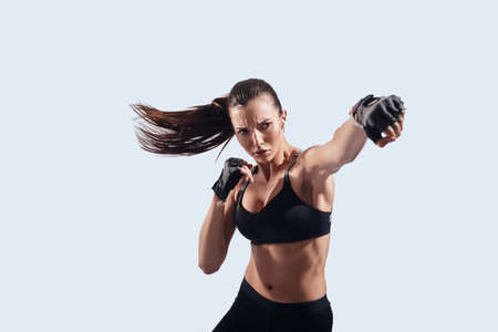 Full of strength. Attractive young woman looking at camera and boxing while standing against grey background