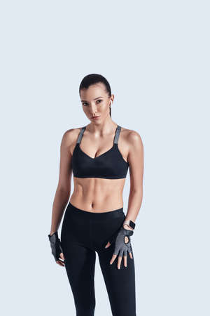 Training to become the best. Attractive young woman looking at camera while standing against grey background Imagens