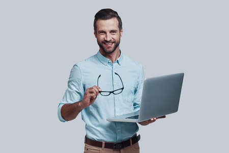 Always ready to help. Good looking young man carrying laptop and looking at camera while standing against grey background Stock fotó
