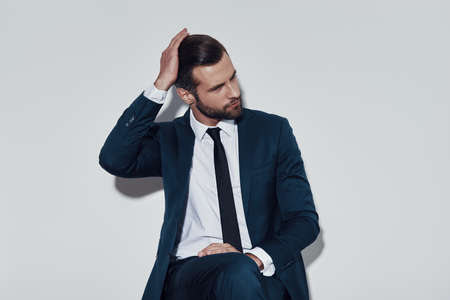 Moment to think. Handsome young man adjusting his hairstyle while sitting against grey background Imagens