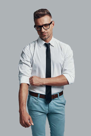 Ready to work. Good looking young man adjusting his sleeve while standing against grey background