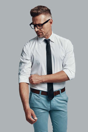 Getting ready to work. Handsome young man adjusting his sleeve while standing against grey background Banco de Imagens