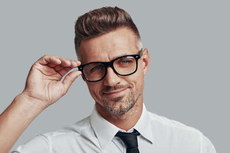 Handsome businessman. Good looking young man adjusting eyewear while standing against grey background Foto de archivo - 124844707
