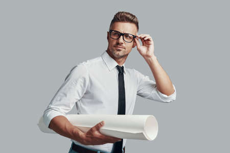 Good looking young man carrying blueprint and adjusting eye wear while standing against grey background