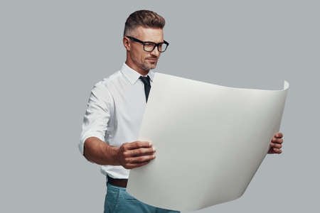 Handsome young man looking at blueprint and smiling while standing against grey background Banco de Imagens