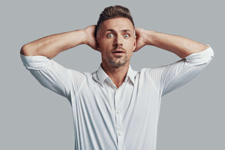 Shocked young man staring at camera and keeping hands behind head while standing against grey background Stock Photo