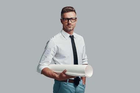 Porträt des Vertrauens. Gut aussehender junger Mann, der Blaupause trägt und mit einem Lächeln in die Kamera schaut, während er vor grauem Hintergrund steht Standard-Bild