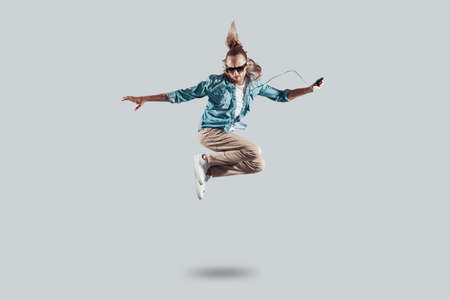 So cool! Full length of handsome young man hovering against grey background Stock Photo