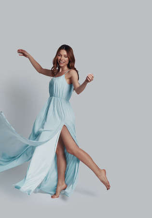 So elegant! Full length of attractive young woman smiling while dancing against grey background