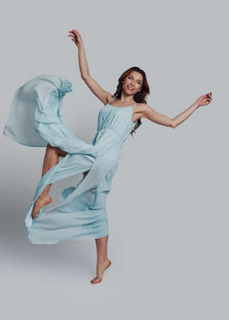 Beauty in motion. Full length of attractive young woman looking at camera and smiling while flying against grey background 写真素材