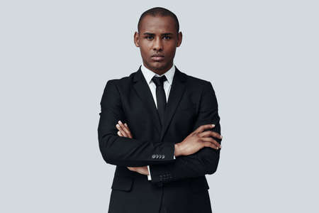 Portrait of confidence. Handsome young African man in formalwear looking at camera while standing against grey background