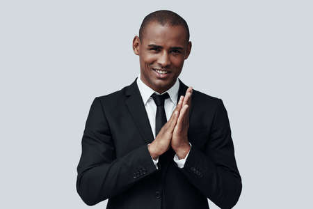 Perfect style. Young African man in formalwear looking at camera and smiling while standing against grey background 写真素材