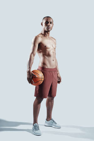 Achieving best results. Full length of handsome young African man in sports clothing looking at camera while standing against grey background