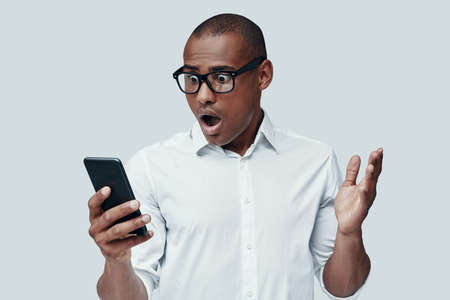 Surprise. Shocked young African man using smart phone while standing against grey background Stock Photo