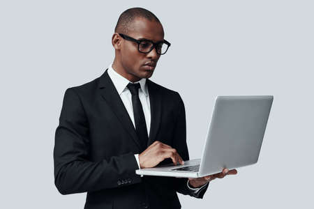 Searching for solution. Young African man in formalwear working using computer while standing against grey background Banque d'images