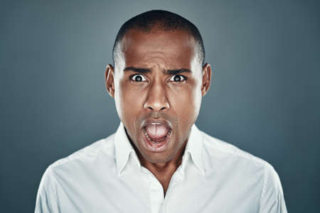 What?! Shocked young African man in shirt looking at camera and making a face while standing against grey background