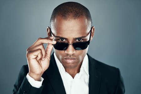 Moderne schoonheid. Charmante jonge Afrikaanse man in volledig pak die naar de camera kijkt en een bril aanpast terwijl hij tegen een grijze achtergrond staat