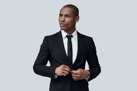 Always perfect. Handsome young African man in formalwear buttoning jacket while standing against grey background