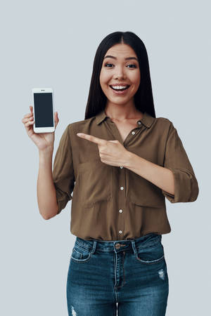 Par ici! Jolie jeune femme asiatique pointant sur un téléphone intelligent et souriant en se tenant debout sur fond gris