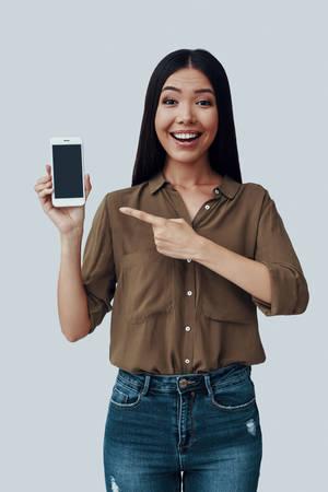 quaggiù! Attraente giovane donna asiatica che punta sullo smartphone e sorride mentre è in piedi su uno sfondo grigio