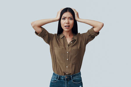 What is happening? Confused young Asian woman making a face while standing against grey background Reklamní fotografie