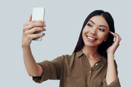 Time for selfie. Attractive young Asian woman taking selfie and smiling while standing against grey background
