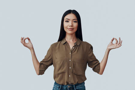 Finding balance. Attractive young Asian woman looking at camera and smiling while standing against grey background