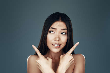Confused young Asian woman looking away and making a face while standing against grey background