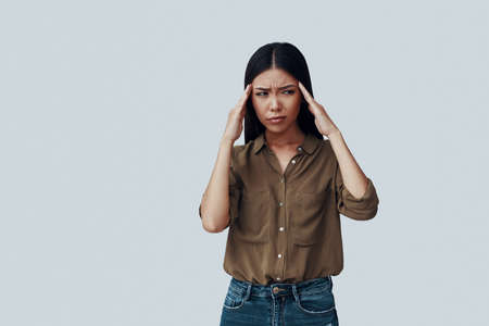Frustrated young Asian woman making a face while standing against grey background