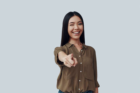 Beautiful young Asian woman looking at camera and smiling while standing against grey background 写真素材