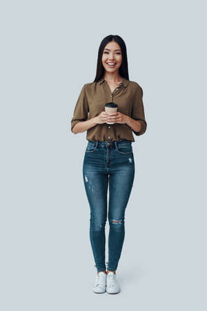 Full length of attractive young Asian woman looking at camera and smiling while standing against grey background