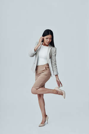 Todo debería estar perfecto. Longitud total de atractiva joven asiática ajustando tacones altos mientras está de pie contra el fondo gris