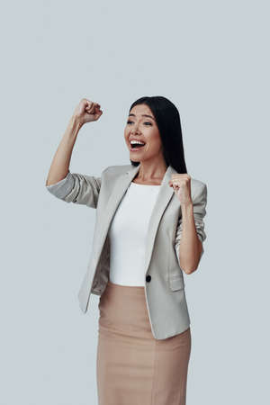 I did it! Attractive young Asian woman gesturing and smiling while standing against grey background