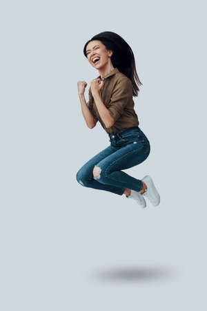 Success. Full length of beautiful young Asian woman gesturing and smiling while hovering against grey background Imagens