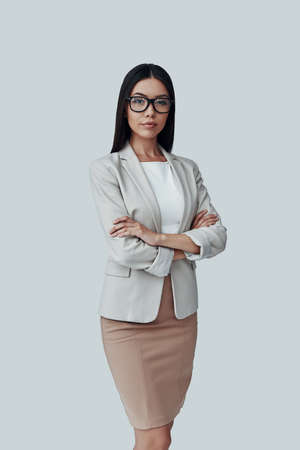 Intelligence. Attractive young Asian woman looking at camera and smiling while standing against grey background Imagens