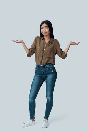 Uncertainty. Full length of beautiful young Asian woman looking at camera while standing against grey background