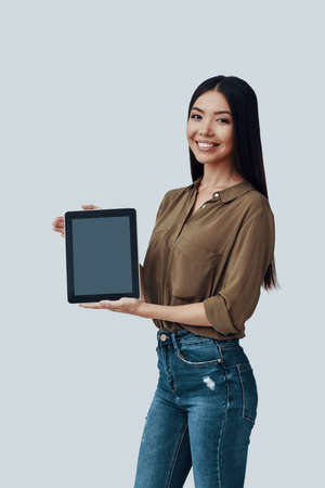Look here! Beautiful young Asian woman looking at camera and smiling while standing against grey background