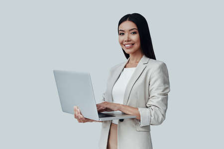 How may I help you? Attractive young Asian woman looking at camera and smiling while standing against grey background Imagens
