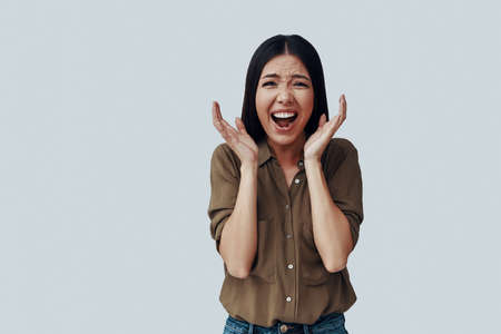 Oh my God! Surprised young Asian woman making a face while standing against grey background Imagens