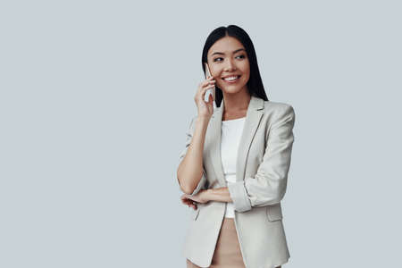 Pleasant talk. Attractive young Asian woman talking on the phone and smiling while standing against grey background