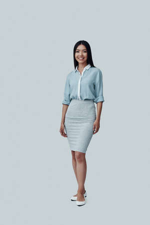 Young and beautiful. Full length of attractive young Asian woman looking at camera and smiling while standing against grey background Imagens