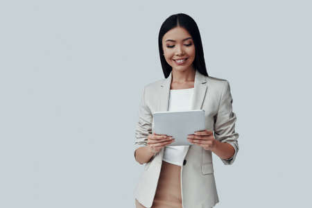 Confident expert. Attractive young Asian woman using digital tablet and smiling while standing against grey background